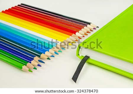 Colorful pencils and green notebook on white background