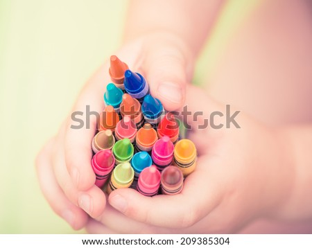colorful pencils in child arms