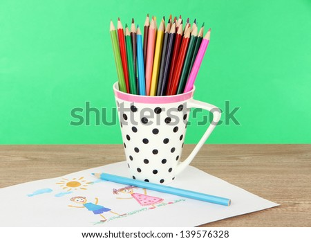 Colorful pencils in cup on table on green background