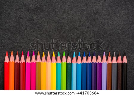 colorful pencils linned up on dark slate background - stock photo
