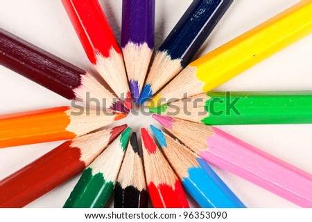 Colorful pencils lying in a circle on a white surface