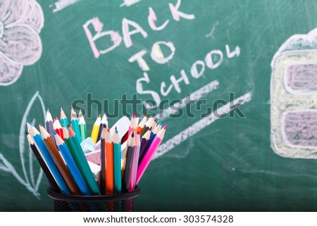Colorful pencils of red yellow orange violet purple pink green and blue in stationary cup on written with chalk back to school on blackboard background copyspace, horizontal picture - stock photo