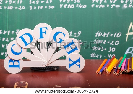 Colorful pencils of red yellow orange violet purple pink green and blue near stationary cup ruler and fan english alphabet standing on brown school desk on written with white chalk blackboard on math - stock photo