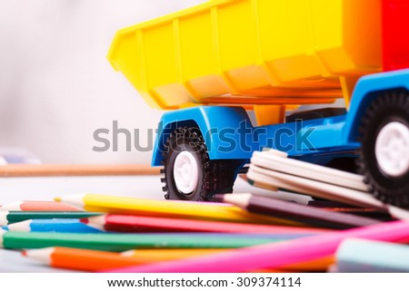 Colorful pencils of red yellow orange violet purple pink green blue chalk fan english alphabet and truck car toy lying on white school desk background, horizontal photo - stock photo