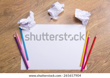 colorful pencils on clear white paper with crumble paper balls on wooden table background - stock photo