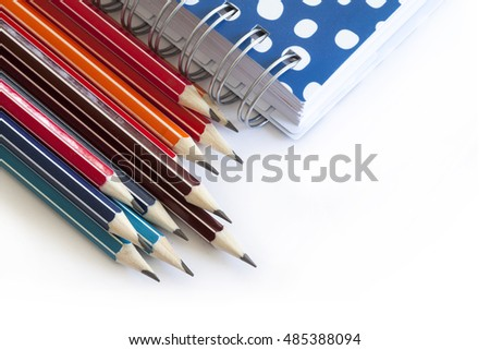 Colorful pencils on white background and  notebook
