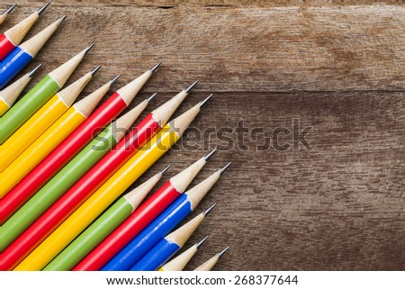 colorful pencils on wooden background - stock photo
