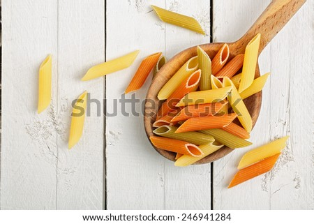 colorful penne pasta on wooden ladle  - stock photo