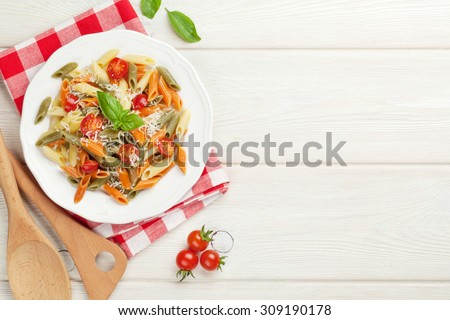 Colorful penne pasta with tomatoes and basil on wooden table. Top view with copy space - stock photo