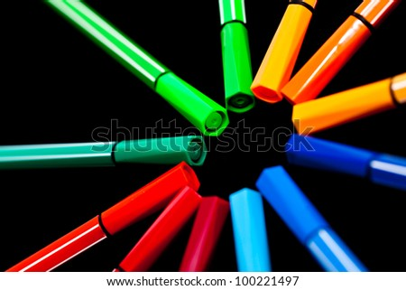 Colorful pens on black background.