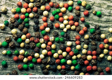 Colorful peppercorns on an old wooden table. Toned.