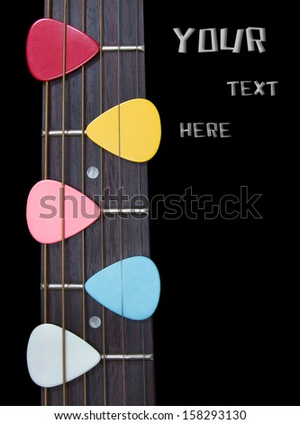 colorful picks on guitar-fingerboard isolated - stock photo