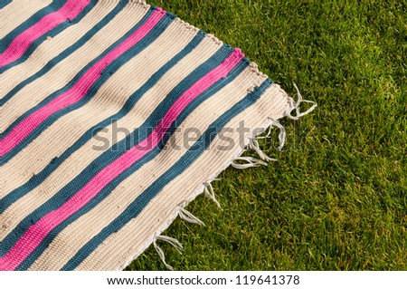 colorful picnic blanket on the grass field - stock photo