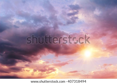 Colorful, picturesque sky background with sun and huge dark rain clouds. - stock photo