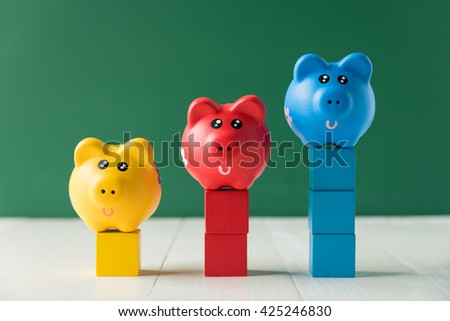 Colorful piggy bank on stack of wood cube building blocks - stock photo