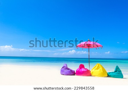 colorful pillows and bright umbrella on tropical sea and beach background, vacation in tropics - stock photo