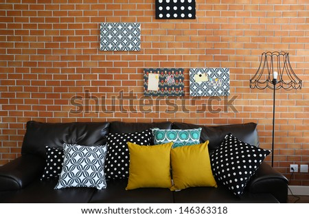 Colorful pillows on a sofa with brick wall in background - stock photo