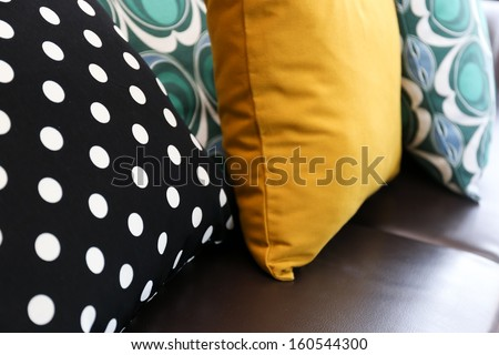 Colorful pillows on leather sofa - stock photo