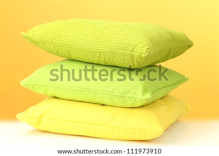 Colorful pillows on table on yellow background