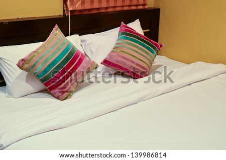 Colorful pillows on white bed - stock photo