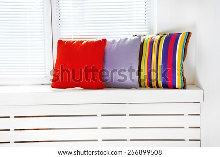 Colorful pillows on windowsill