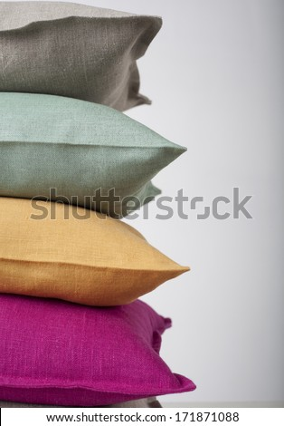 Colorful pillows stack isolated on white - stock photo