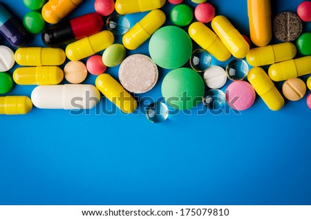 colorful pills and tablets on blue background - stock photo