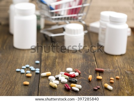 Colorful pills and various pill bottles on dark wooden background