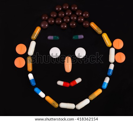 Colorful pills in a vase as a face