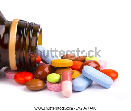 Colorful pills spread in front of a pill bottle. - stock photo