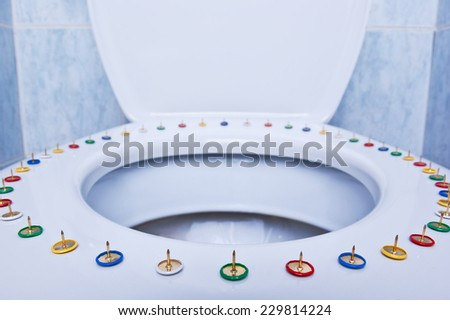 Colorful pins on a toilet seat - stock photo