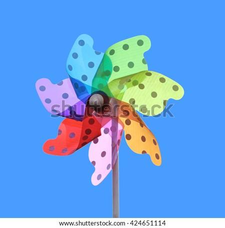 Colorful pinwheel on blue background - stock photo