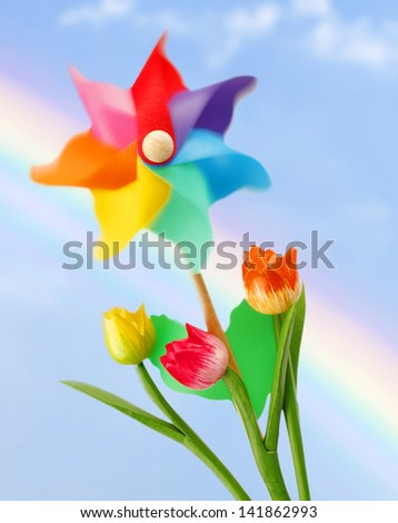 Colorful pinwheel on blue sky with rainbow