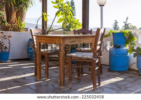 Colorful plants, tables and chairs in front of a tavern early in the morning in the village Pitsidia in south Crete.  - stock photo