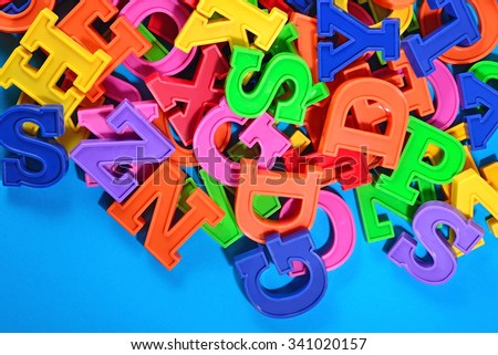 Colorful plastic alphabet letters on a blue background