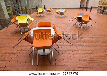 Colorful plastic and aluminum chairs leaning against tables at a cafe outdoor dining area