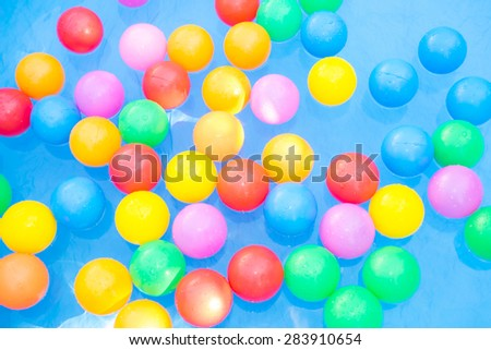 Colorful plastic balls, yellow balls, red balls, green balls, blue balls and pink balls, children toy, floating on the water in the kiddie pool for background.