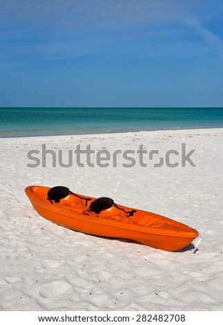 Colorful plastic canoe on a white sandy sandy beach - stock photo
