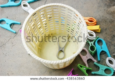 Colorful plastic clothes pins on cement floor with one steel cloth pin in a basket