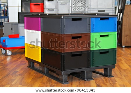 Colorful plastic crates and boxes at transportation pallet