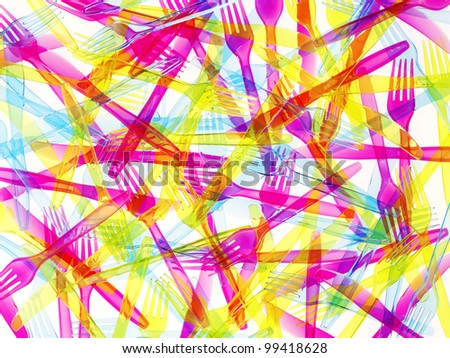 Colorful plastic cutlery background - stock photo