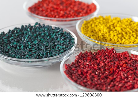 Colorful plastic granules in glass - stock photo