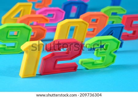 Colorful plastic numbers 123 close up on a blue background