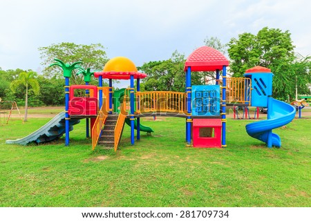 colorful plastic playground on green lawn in the public park - stock photo