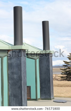 Colorful plastic public pit toilet buildings by the beach - stock photo