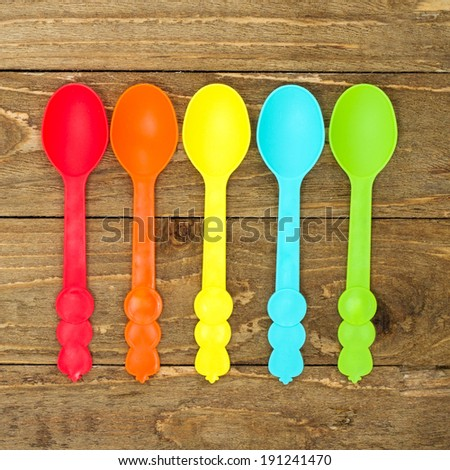 Colorful plastic spoons on a vintage background with copy space - stock photo