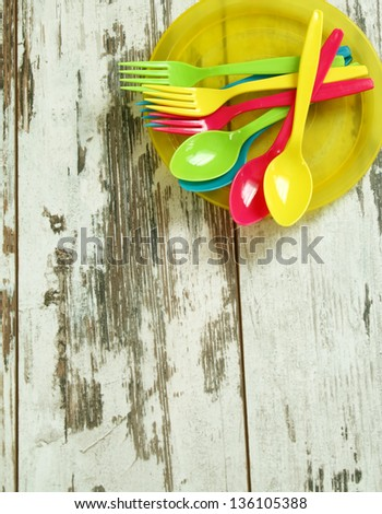 colorful plastic tableware on wooden boards - stock photo