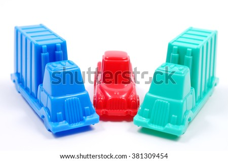 Colorful plastic toy cars of different colors on a white background. Trucks blocked the car. Close up view, selective focus. - stock photo
