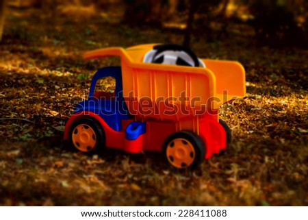 Colorful plastic toy dumpster truck with a hardhat in the back standing on the ground outdoors in the garden in the shade of a tree, side view - stock photo