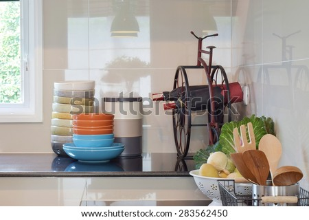 Colorful plates and bowls and wine bottles on black granite top in the kitchen - stock photo